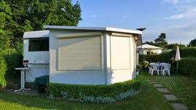 Caravan con una veranda fissa fatta del tessuto della tenda, delle finestre di scivolamento di vetro e dei ciechi su un campeggio fotografie stock libere da diritti