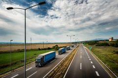 Caravan or convoy of blue lorry trucks on highway. Caravan or convoy of blue lorry trucks in line on a country highway stock images