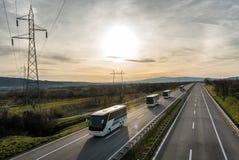 Caravan or convoy of busses on highway. Caravan or convoy of busses in line on a country highway Royalty Free Stock Image