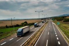 Caravan or convoy of lorry trucks on highway. Caravan or convoy of lorry trucks in line on a country highway royalty free stock image