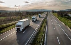 Caravan or convoy of trucks on highway. Caravan or convoy of trucks in line on a country highway Royalty Free Stock Photos
