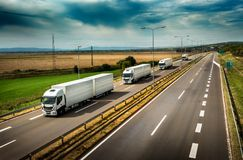 Caravan or convoy of White Lorry trucks on highway. Caravan or convoy of White Lorry trucks in line on a country highway stock photo