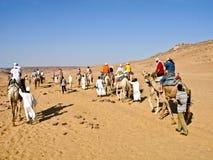 Caravan crossing the Nubian desert. ASWAN, EGYPT - AUGUST 23: A caravan of tourists in camels crossing the Nubian desert on August 23, 2010 stock photos