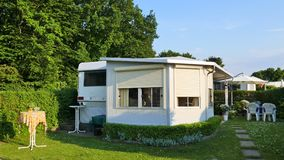 Caravan with a fixed veranda made of awning fabric, glass sliding windows and blinds on a German campsite. stock image