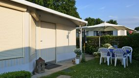 Caravan with a fixed veranda made of awning fabric, glass sliding windows and blinds on a German campsite. stock photo