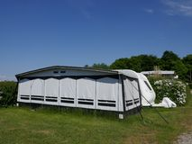 Caravan on a German campsite with a weather proofed tent in front of it. The windows are closed stock image
