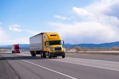 Caravan moderne semi vrachtwagens op rechte weg op plateau Royalty-vrije Stock Foto's