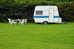 Caravan. An old fashioned caravan with garden furniture parked in a garden Stock Photography