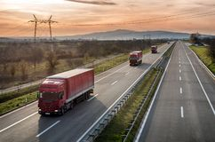 Caravan of Red Lorry trucks on highway. Caravan or convoy of Red Lorry trucks in line on a country highway royalty free stock photos