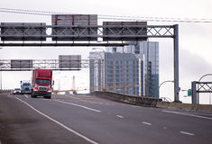 Caravan of semi trucks going by wide interstate highway. Convoy of big rigs American semi trucks with various types of trailers moving along overpass wide Royalty Free Stock Photography