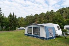 Caravan and shelter at the camping Stock Image