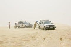 The caravan of SUVs stuck in the Sahara desert in a sandstorm. stock photography