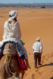 Caravan of tourists in desert. The woman and its guide going across Sahara Royalty Free Stock Photography