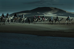 Caravan of tourists passing desert lake on camels. In moonlight Royalty Free Stock Image
