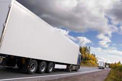 Caravan of trucks on highway. Caravan of trucks, highway, truck slightly blurred in motion royalty free stock photo