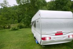 Caravan van in the green meadow camping Stock Photo