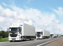 Caravan van witte vrachtwagens op weg Royalty-vrije Stock Afbeeldingen