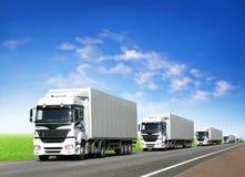 Caravan van witte vrachtwagens op weg onder blauwe hemel stock fotografie