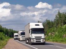 Caravan of white trucks on highway. Caravan of white trucks on summer country highway Scandinavia stock image