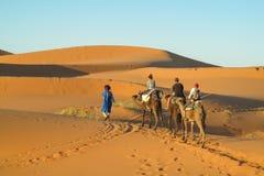 Caravana del camello en dunas del desierto de la arena de África Foto de archivo