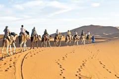 Caravana del camello que pasa a través de las dunas de arena en Sahara Desert, Foto de archivo