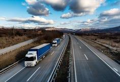 Caravana ou trem de caminhões do caminhão na estrada do país imagem de stock