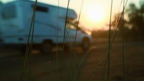 Caravana que conduce abajo de un camino de tierra en la puesta del sol metrajes