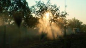 Caravana que golpea para arriba el polvo con el pie en la puesta del sol almacen de video