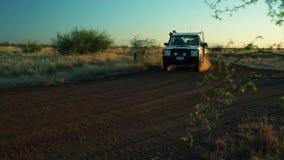 Caravana que golpea para arriba el polvo con el pie en la puesta del sol metrajes