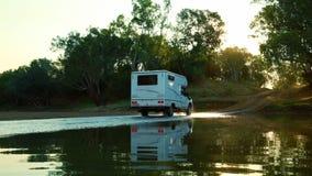 Caravana que para más allá de un poco de agua en la puesta del sol almacen de video