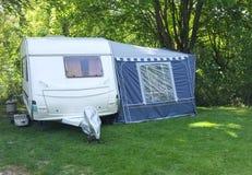 Caravana y toldo, el acampar del arbolado Imagen de archivo libre de regalías