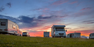 Caravans and cars campsite sunset Royalty Free Stock Photos