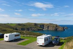 Caravans on a pitch by a beautiful coast scene Royalty Free Stock Photography
