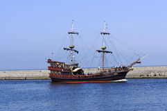 Caravele leaving a port. Antique caravele ship leaving port in sunny day royalty free stock image