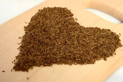 Caraway heart. Heart formed from caraway on a wooden board Stock Photo