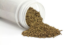 Caraway seeds spilling from container Stock Images