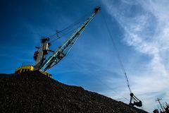 Carbón cargado de la grúa del puerto contra un cielo azul y las nubes imagenes de archivo