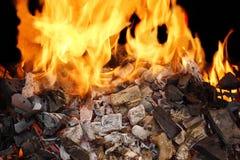 Carbón de leña ardiente y una llama brillante Foto de archivo
