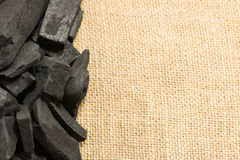 Carbón de leña negro en fondo de la textura del saco de yute Imágenes de archivo libres de regalías