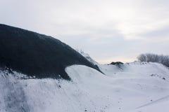 Carbón en el almacén abierto debajo de la nieve Foto de archivo libre de regalías