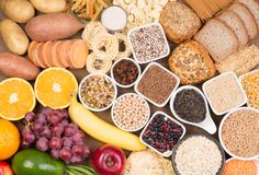 Carbohydrates food sources, top view on a table. Carbohydrates food sources such as bread, pasta, grains, vegetables and fruit, top view on a table stock photo
