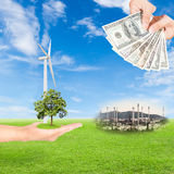 Carbon credits concept. Hand holding tree and wind turbine and US Dollars banknote with oil refinery plant against green field and blue sky background royalty free stock photo