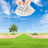 Carbon credits concept. Hand holding wind turbine, solar panels, tree and US Dollars banknote against green field and blue sky background royalty free stock photo