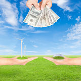 Carbon credits concept. Hand holding wind turbine, solar panels and US Dollars banknote against green field and blue sky background royalty free stock photo