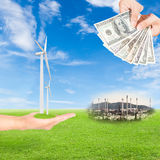 Carbon credits concept. Hand holding wind turbine and US Dollars banknote with oil refinery plant against green field and blue sky background stock images