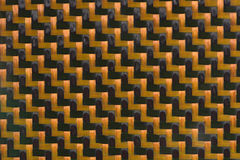 Carbon fiber background. Detail of carbon fiber panel with orange thread Stock Photo