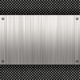 Carbon fiber metal plate. Carbon fiber background with a riveted piece of brushed aluminum plate. Plenty of copyspace in this layout Royalty Free Stock Photos