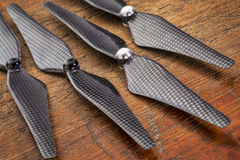 Carbon fiber self-tightening drone propellers. Set  of four carbon fiber self-tightening propellers for a quadcopter drone against grunge wood Royalty Free Stock Photos