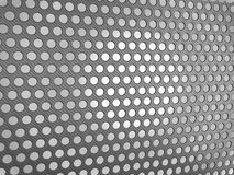 Carbon fibre surface with holes. Over studio light background Royalty Free Stock Photo