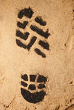 Carbon Footprint. A bootprint in sand to illustrate a carbon footprint Stock Photo